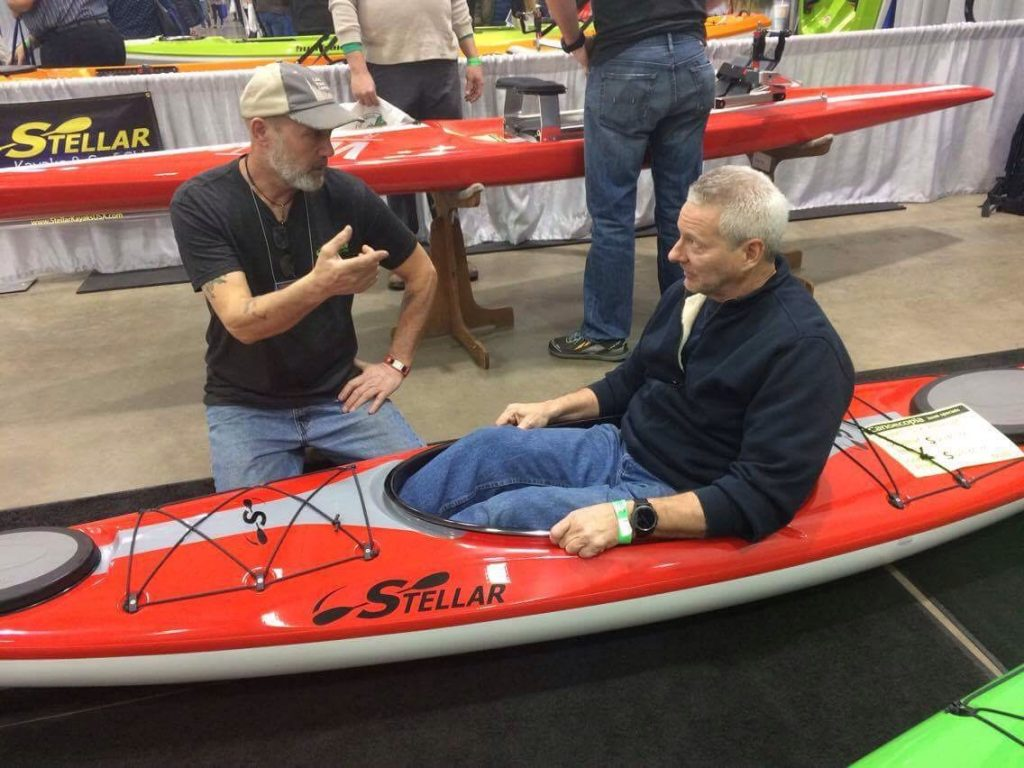 Joe Zellner talking with a customer in a Stellar Kayak.