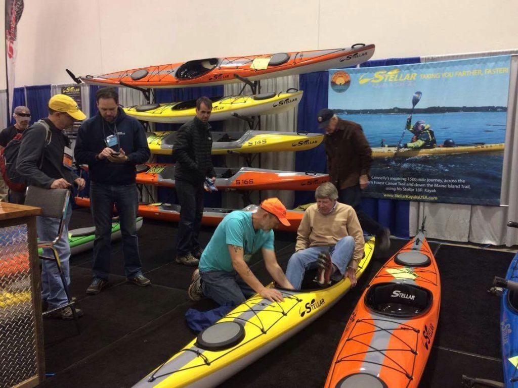 Joe Zellner showing customer how to sit in a Stellar Kayak.