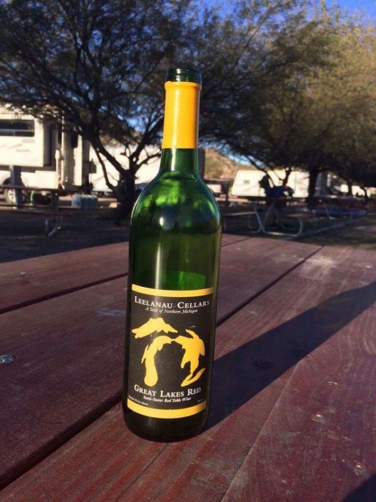 Leelanau Cellars Great Lakes Red wine bottle on picnic bench.