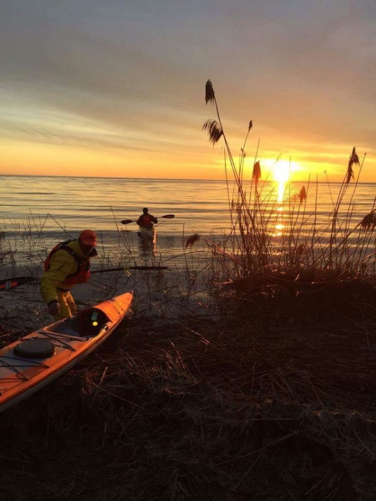 2 Paddling 5 entering water with Kayaks on the morning sunrise.
