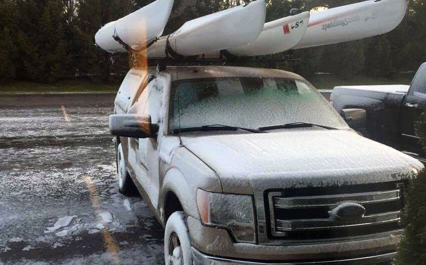 Snow on truck with kayaks on rack.