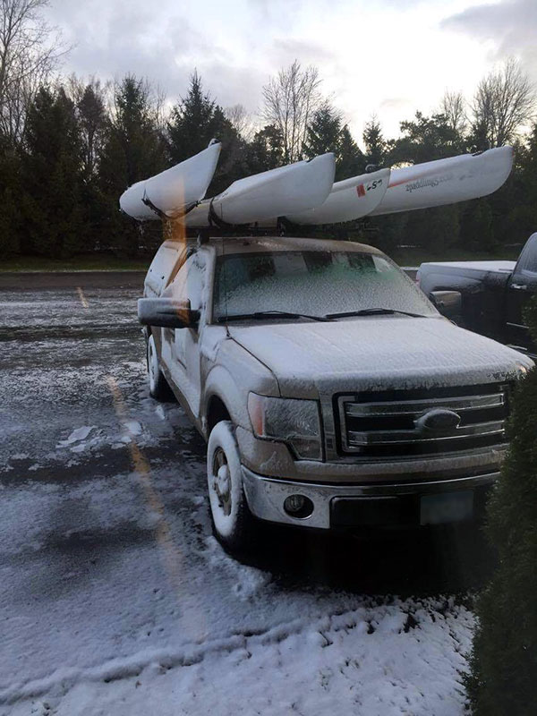 Snow on truck with kayaks on rack full size picture.