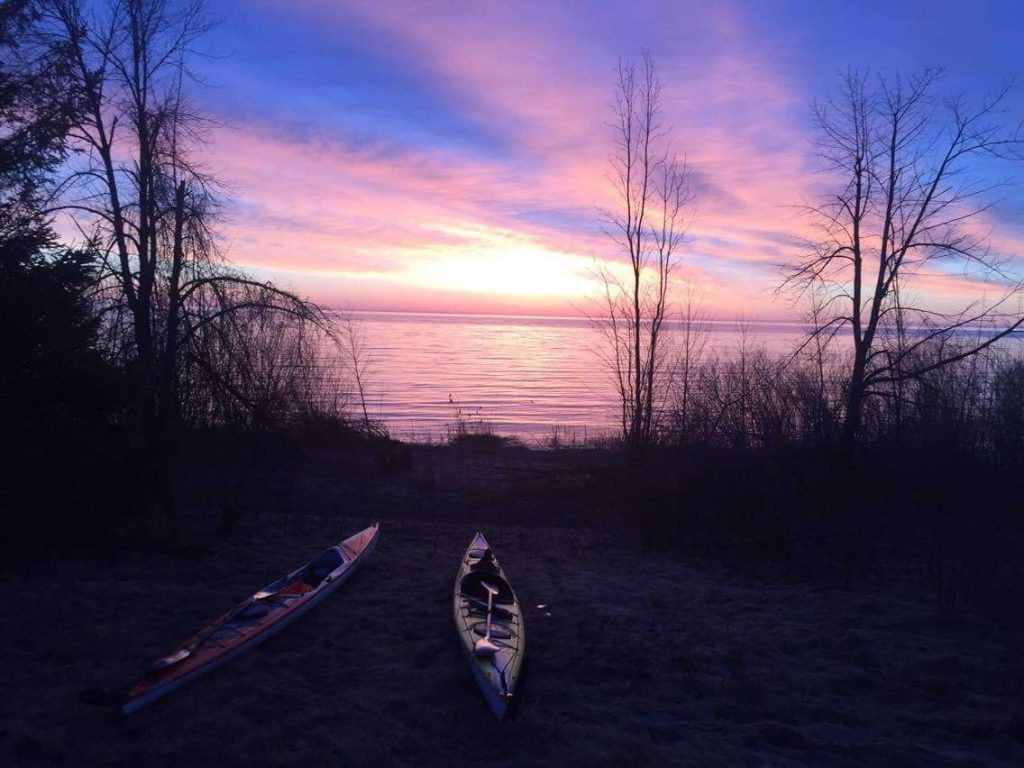 Kayaks by lake Huron during a morning sunrise.