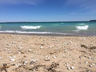 Blue water waves and sandy beaches with rocks near Glen Haven, Michigan.