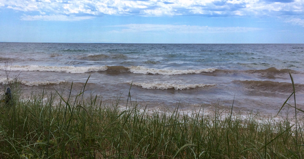 Northern Lake Michigan near Seul Choix Lighthouse. View of grassy beach and rough waters with a blue sky.