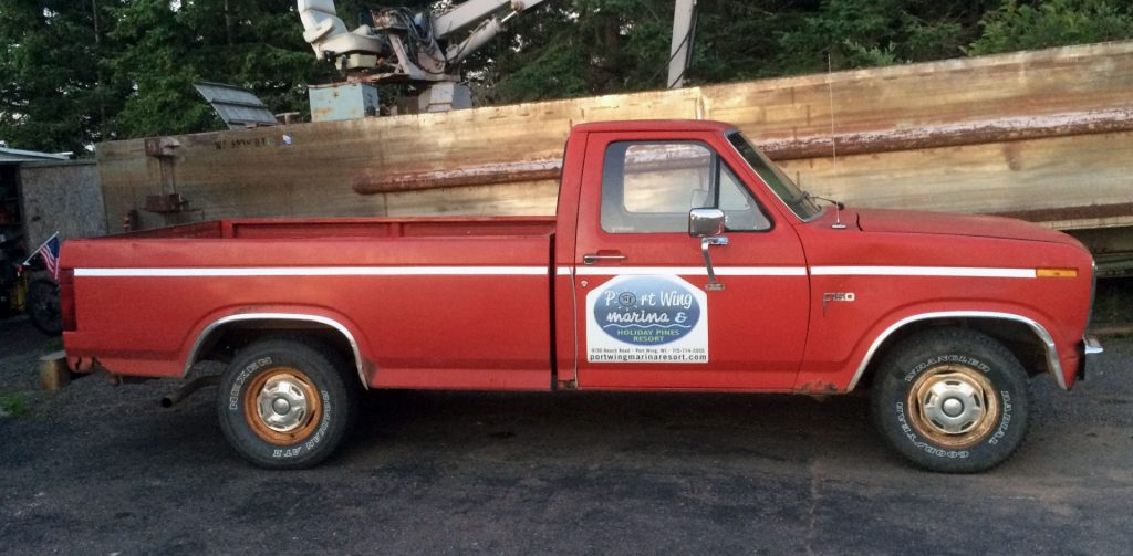 Red 1985 Ford pickup for Port Wing Marina & Holiday Pines Resort.