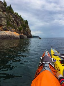 Kayaking on Lake Superior with the Split Rock Lighthouse in the distance.