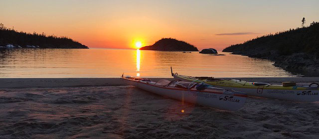 Sunset near Marathon Ontario, Canada with kayaks on the beach.